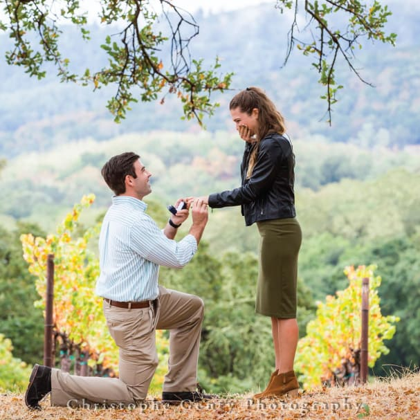 A man kneeling on one knee holds a small open box and looks up at his girlfriend, who is covering her mouth with vineyards in the background.