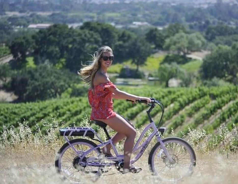 A woman rides an electric bike with scenic rolling vineyards in the background