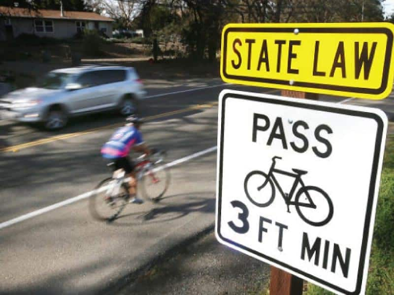 A cyclist rides pas a sign adjacent to Silverado Trail roadway in Napa Valley that reads: State Law, Pass 3 Feet Minimum.