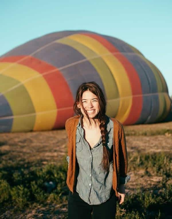 A woman flashes an huge smile in the foreground with a rainbow-colored hot-air balloon deflating on the ground behind her.