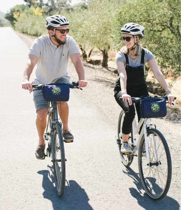 A couple smiles and laughs while biking side by side down a quiet road lined with olive trees in Napa Valley.