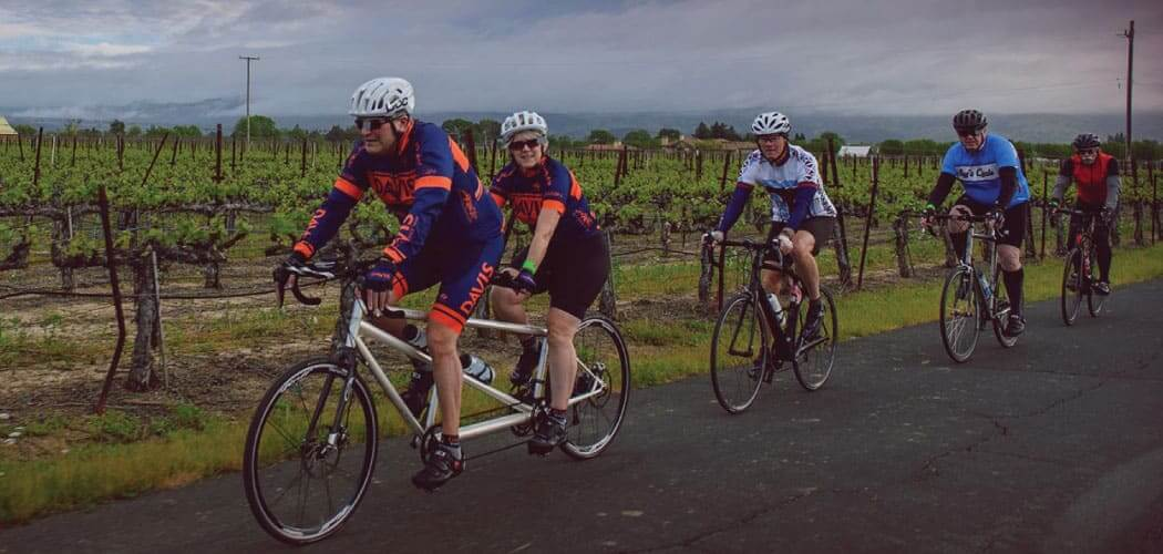 Cyclists riding a tandem ride past vineyards in the Cycle 4 Sight bike ride