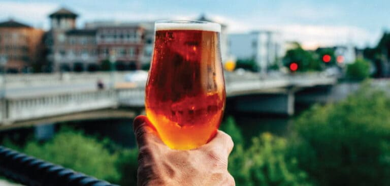 A glass of beer raised in the foreground overlooking the Napa Riverfront