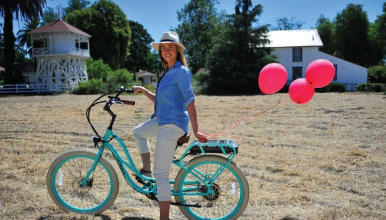 A woman poses with an electric bike with a Napa Valley winery in the background