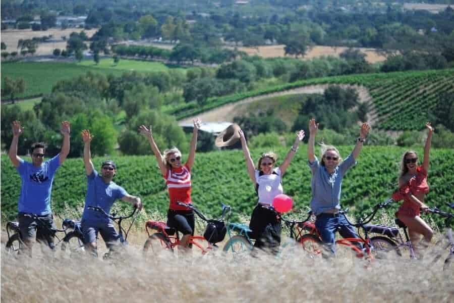 Group of six men and women posing on electric bikes in front of Napa vineyards