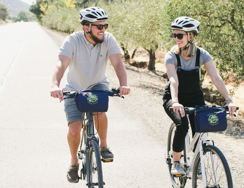 A couple smiles and laughs while biking next to each other on a guided bike tour through Napa Valley.