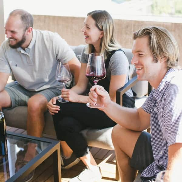 Two men and a woman seated on couches on a winery patio hold wine glasses and laugh during a tasting.