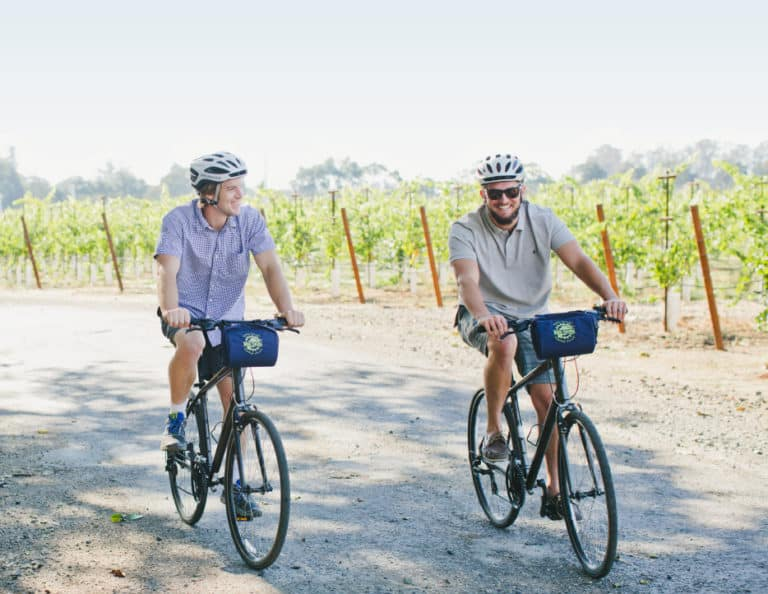Two men ride bikes side by side next to vineyards while on a guided bike tour.