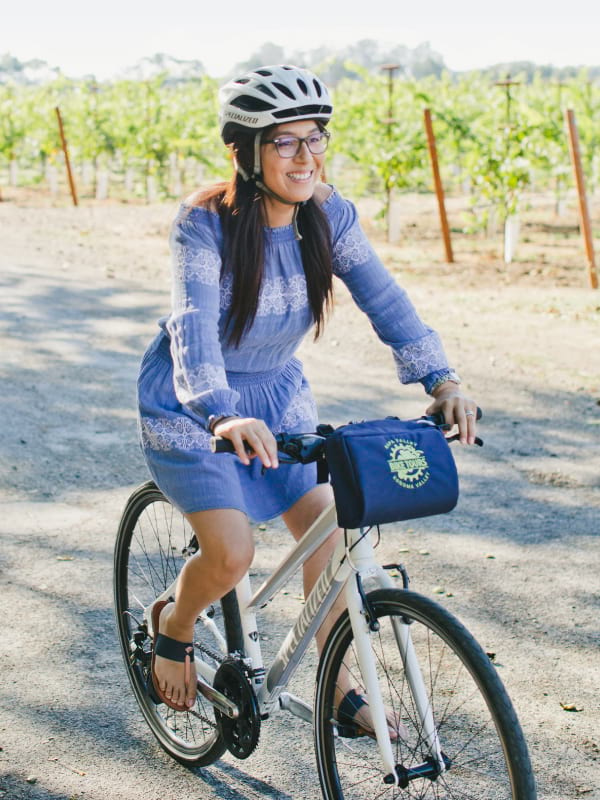 A woman smiles while biking past a vineyard on a quiet road in Napa Valley.