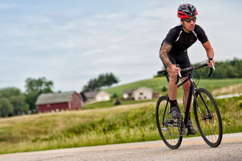 A male and female cyclists ride road bikes on a Napa cycling route past vineyards.